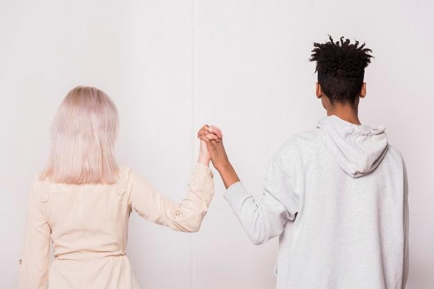 Multi étnica pareja adolescente de pie contra la pared blanca tomados de la mano