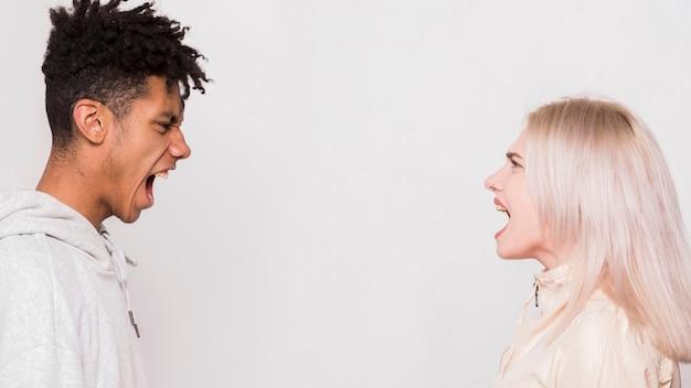 Multi étnica pareja joven de pie cara a cara gritando contra el fondo de la pizca