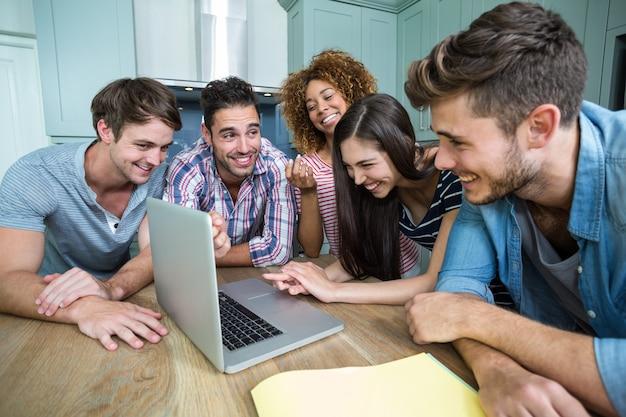 Multi étnicas amigos riendo y mirando en la computadora portátil