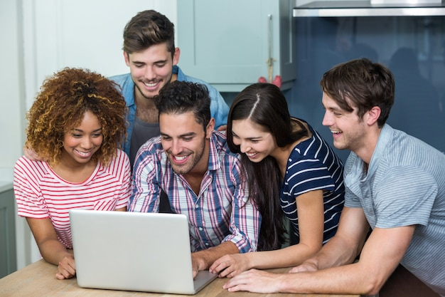Multi étnicas jóvenes amigos mirando en la computadora portátil sobre la mesa