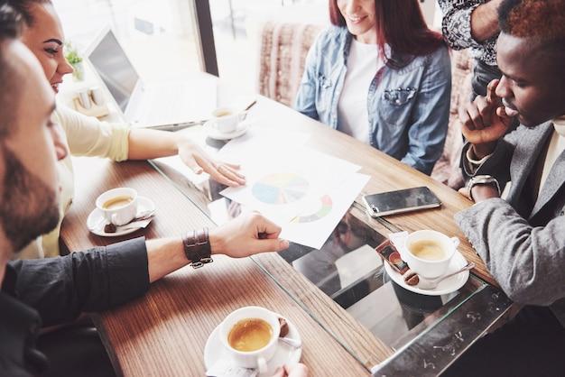 Multi étnico emprendedor, concepto de pequeña empresa. mujer mostrando a sus compañeros de trabajo algo en la computadora portátil mientras se reúnen alrededor de una mesa de conferencias