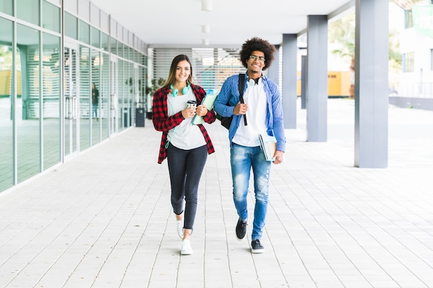 Multi étnicos estudiantes masculinos y femeninos caminando juntos en el campus universitario