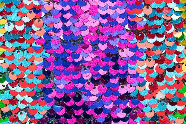 Multicolor hermosa textura de lentejuelas iridiscentes, superficie de tela de escamas de pescado
