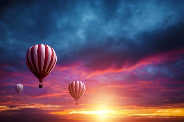 Multicolores, grandes globos en el cielo con el telón de fondo de una hermosa puesta de sol