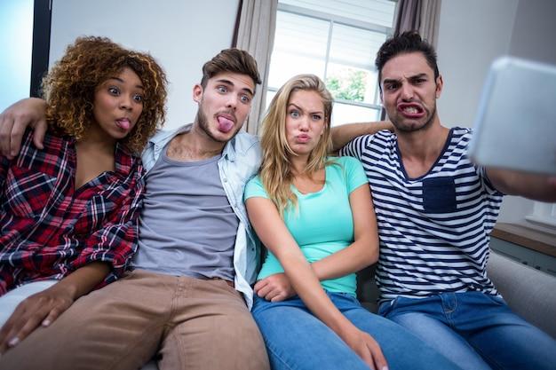 Multiétnicas amigos haciendo muecas mientras se toma selfie en el teléfono celular