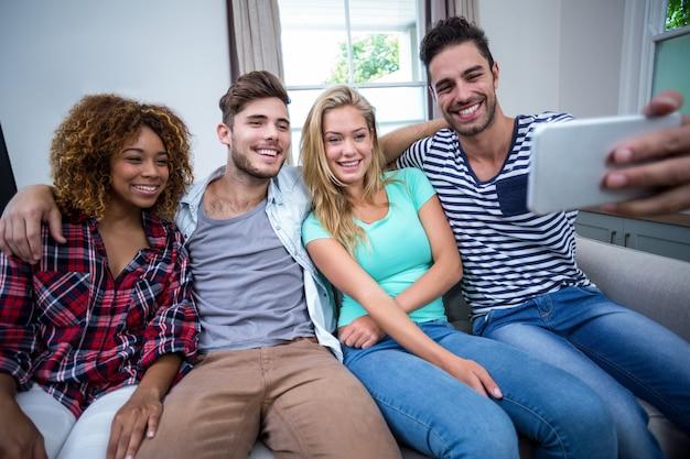Multiétnicas amigos tomando selfie mientras está sentado en el sofá