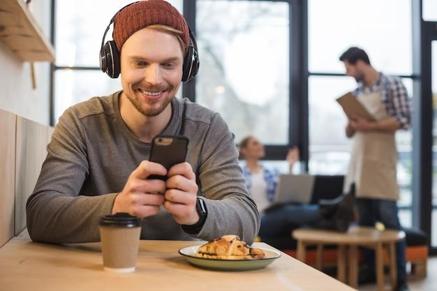Multimedia moderna. encantado de joven positivo sentado en la cafetería y usando audífonos mientras usa su gadget