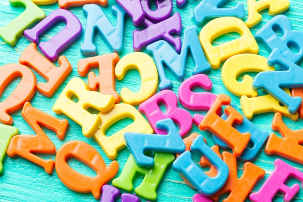 Múltiples letras de colores en la mesa de madera