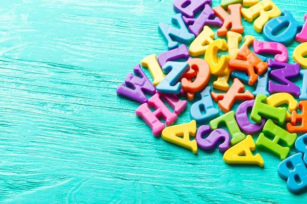 Múltiples letras de colores sobre fondo de madera