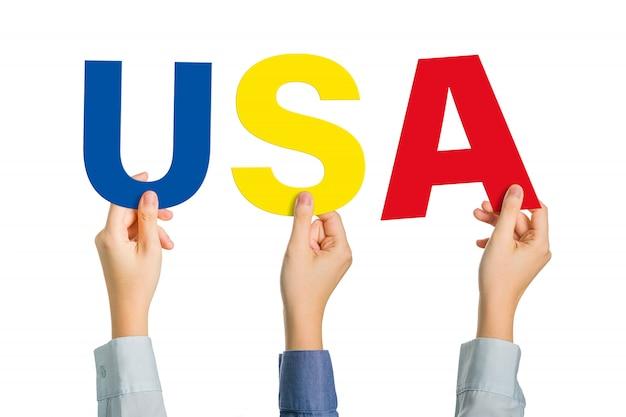 Múltiples manos sosteniendo alfabetos de colores para formar la palabra usa en la pared blanca