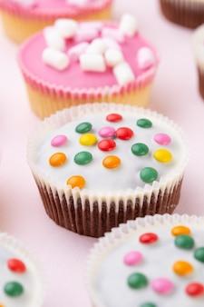 Múltiples muffins de colores muy bien decorados sobre un fondo rosa, vista superior.