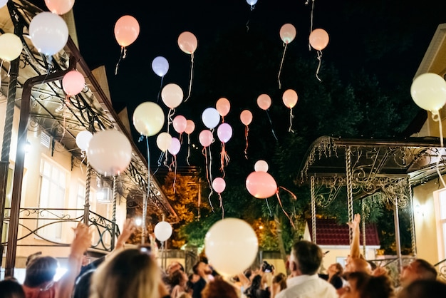 Multitud arrojando globos de colores al cielo por la noche durante el festival