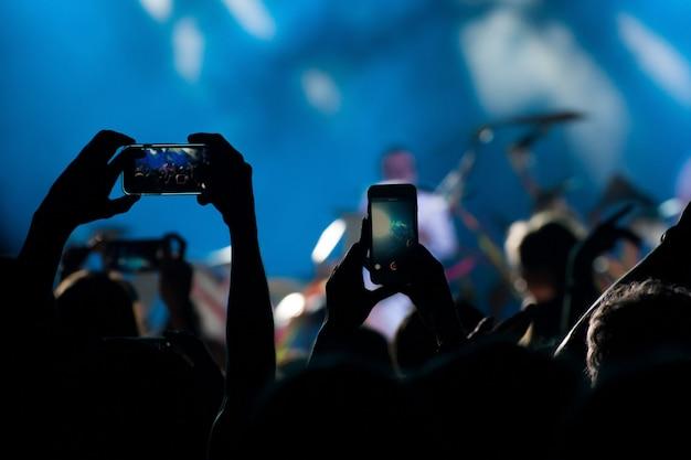 La multitud del concierto toma un video y una foto del concierto por teléfono.