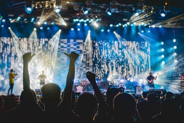 Multitud de conciertos en siluetas del club de fans de música con acción de mostrar la mano que sigue al cantante.