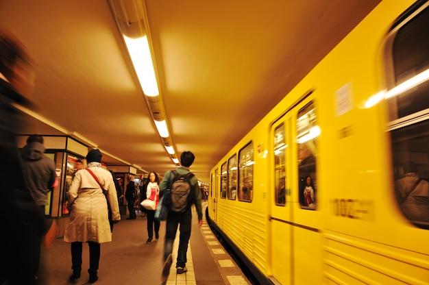 Multitud de gente caminando en el metro, tren en movimiento