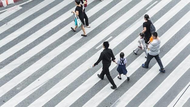 Multitud de personas y un grupo de familias con niños caminan en una calle, cruce peatonal en la calle de la ciudad.