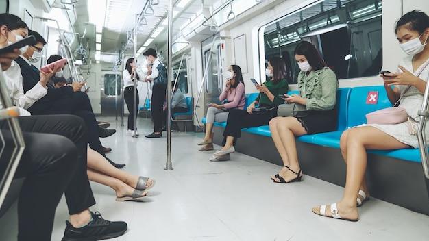 Multitud de personas con máscara facial en un viaje en tren subterráneo público abarrotado