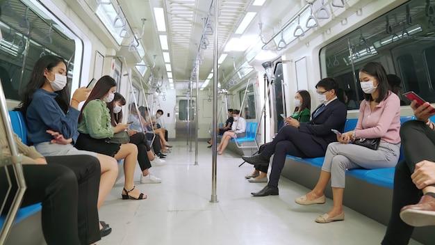 Multitud de personas que llevaban mascarilla en un viaje en tren subterráneo público abarrotado