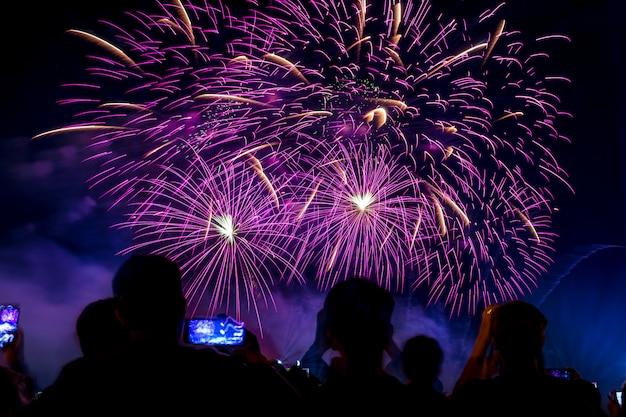 Multitud viendo fuegos artificiales y celebrando ciudad fundada. bellos coloridos fuegos artificiales se muestran en la zona urbana para la celebración en la noche oscura