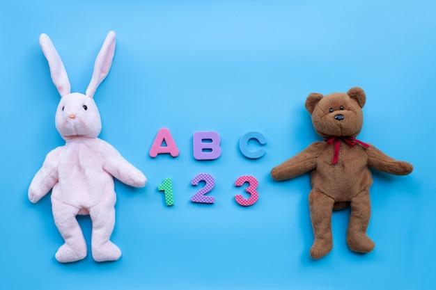 Muñeca de conejo y oso de juguete con alfabeto inglés y números sobre fondo azul. concepto de educación