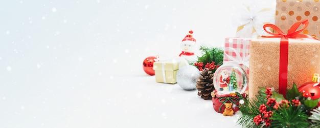 Muñeca de juguete de navidad, árbol de navidad y caja de regalo de vacaciones de año nuevo con adornos decorativos en la mesa de madera blanca con bola de nieve de santa claus. concepto de fondo de banner de regalos y felicitaciones.
