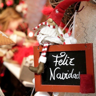 Muñeca de lana con un vestido blanco sentada en una pizarra negra donde se puede leer feliz navidad escrito en español
