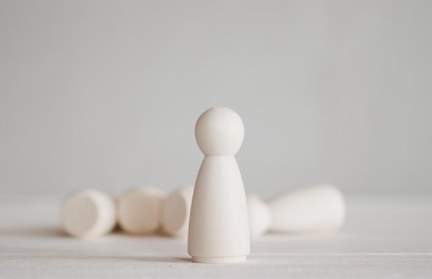 Muñeca de madera de pie delante del grupo que cae