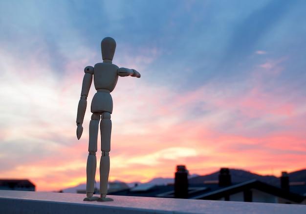 Muñeco de madera apuntando con su dedo hacia el horizonte.