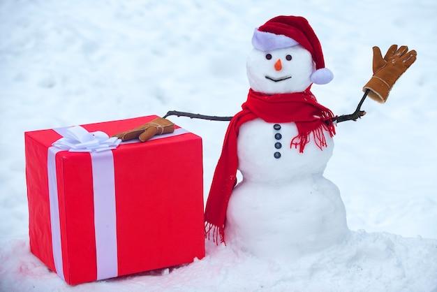 Muñeco de nieve el amigo está de pie con sombrero de invierno y bufanda con nariz roja. muñeco de nieve de navidad en blanco