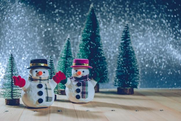 Muñeco de nieve con árbol de navidad y adornos. fondo de brillo