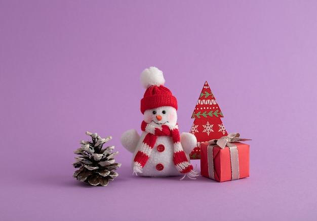 Muñeco de nieve, caja de regalo roja, piña de pino y un árbol de navidad de papel en la habitación morada