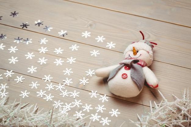 Muñeco de nieve y decoración navideña en mesa de madera