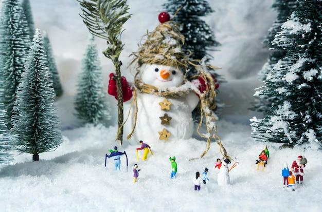 Muñeco de nieve y gente en bosques de pinos durante el invierno