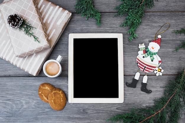 Muñeco de nieve de juguete cerca del marco de fotos, regalos, ramitas, taza de bebida y galletas