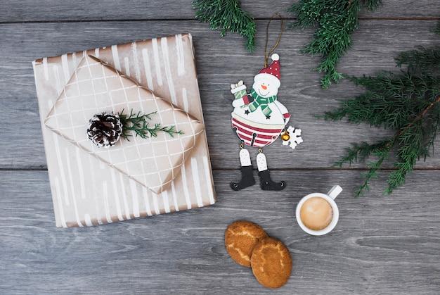 Muñeco de nieve de juguete cerca de regalos envueltos con ganchos, ramitas, taza de bebida y galletas