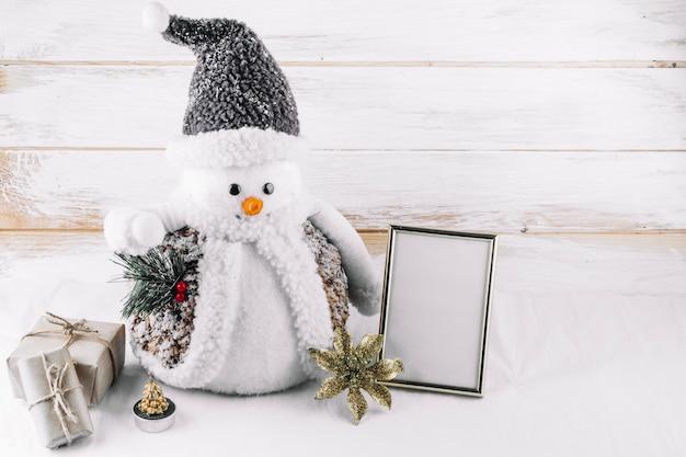 Muñeco de nieve con marco en blanco en la mesa