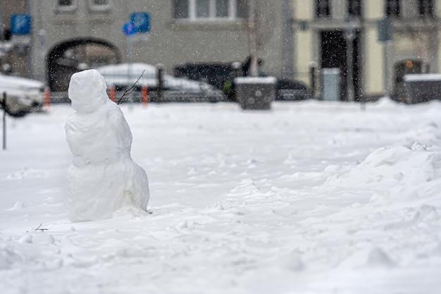 Muñeco de nieve en el patio de una casa residencial, aislado en una superficie urbana desenfocada