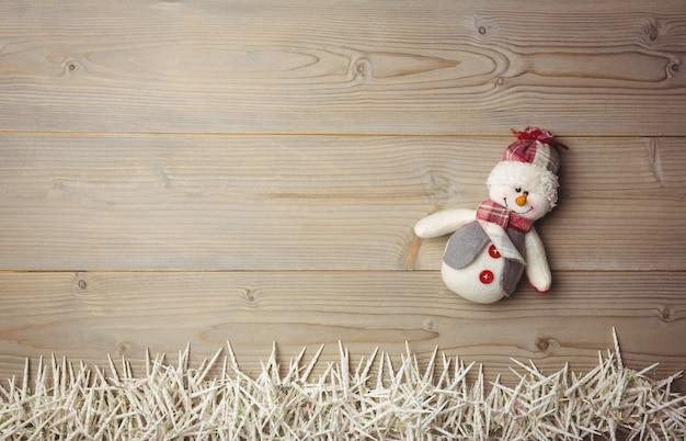 Muñeco de nieve y pequeñas velas en la mesa de madera