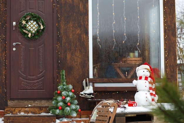 Muñeco de nieve de pie delante de la casa en las vacaciones de navidad