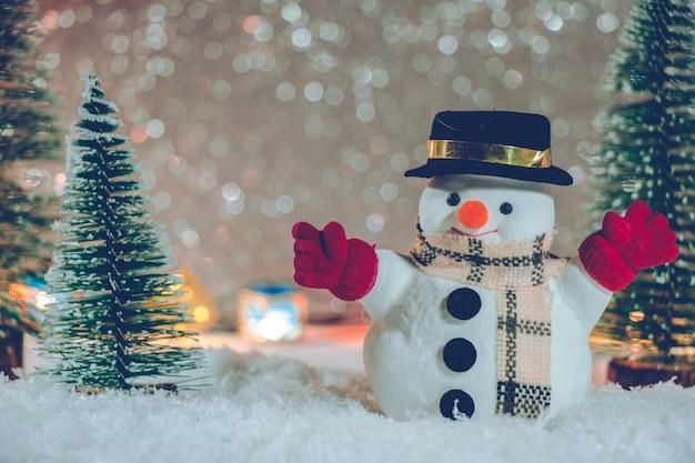 Muñeco de nieve de pie en un montón de nieve en la noche silenciosa con árbol de navidad y adornos