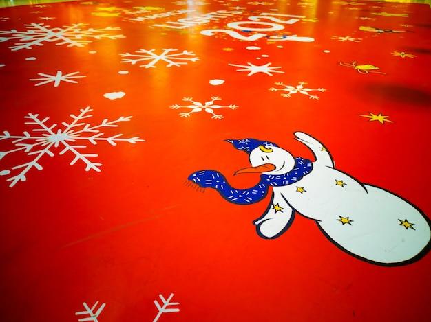Muñeco de nieve sobre fondo rojo con copos de nieve