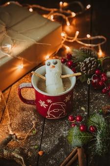 Muñeco de nieve en la taza de café en la mesa de navidad