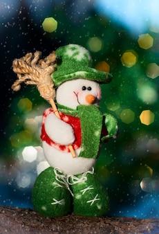 Muñeco de nieve textil en un tronco