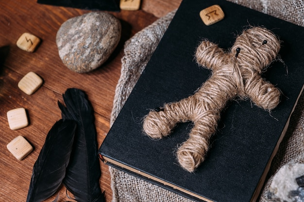 Un muñeco vudú hecho de cuerda yace sobre un libro negro, rodeado de objetos rituales mágicos, plano