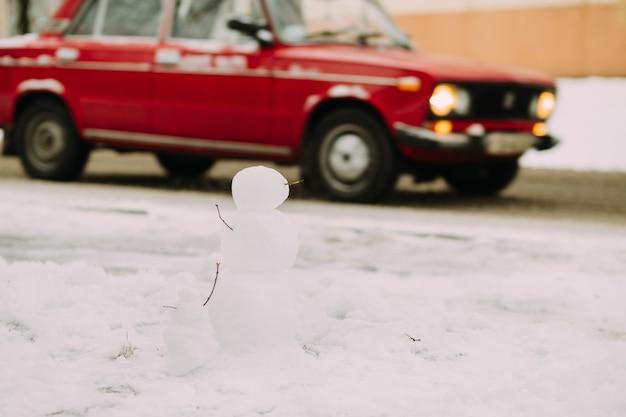 Muñecos de nieve en la carretera con auto rojo