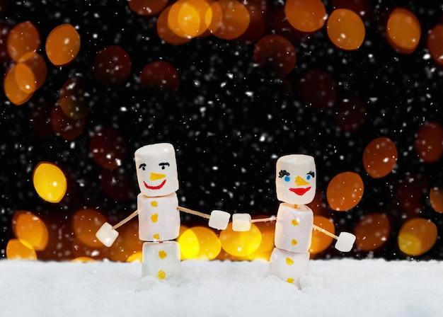 Muñecos de nieve de malvavisco cogidos de la mano. concepto de vacaciones. fondo de navidad con dulces.