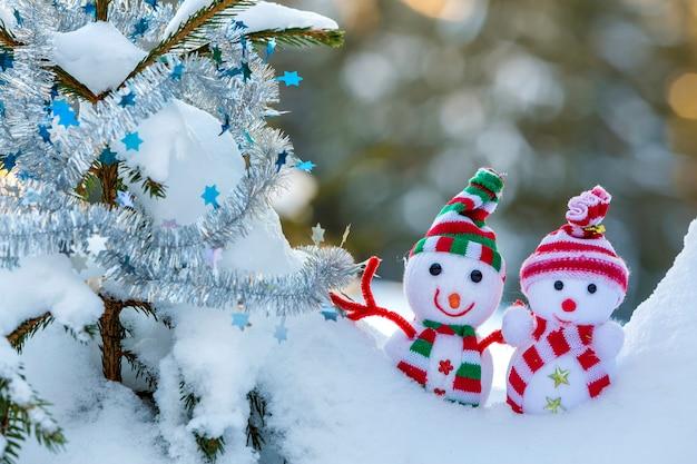 Muñecos de nieve con sombreros de punto y bufandas en la nieve profunda cerca de la rama de pino.