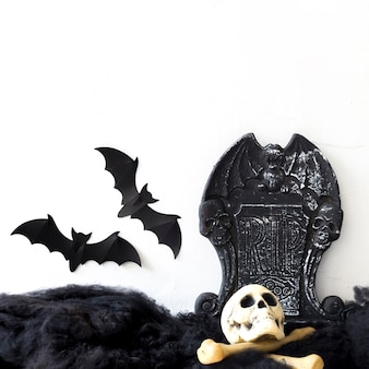 Murciélagos cerca de lápida y huesos