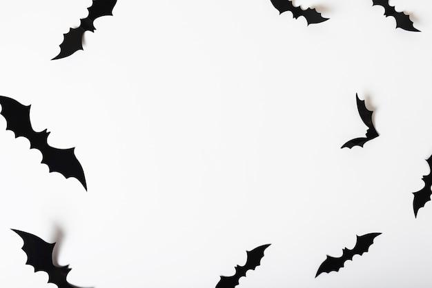 Murciélagos de papel colgando de la pared blanca