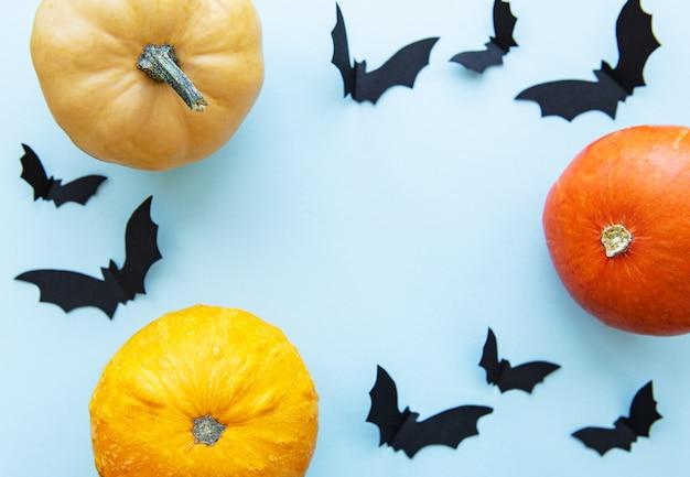 Murciélagos de halloween y calabazas sobre fondo azul.